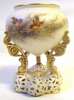 A Royal China Works Worcester Blush Ivory Pedestal Pot Pourri, with pierced scroll shapped base and with three gilded scroll supports hand painted with robins amongst the foliage