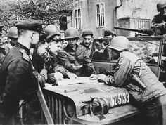 """American and Russian soldiers meet and examine a map at the Elbe River linkup in Torgau, Germany on April 25, 1945. Note the 69th Infantry Division patch on the U.S. soldier, and that he is carrying his service .45 M1911A1 """"cocked and locked"""" in an issue shoulder holster."""