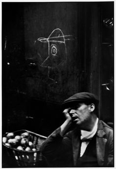 """Henri Cartier-Bresson – Barcelona. Barrio Chino. 1933 - """"The narrow street of Barcelona's roughest quarter is the home of prostitutes, petty thieves and dope peddlers. But I saw a fruit vendor sleeping against a wall and was struck by the surprisingly gentle and articulate drawing scrawled there."""""""