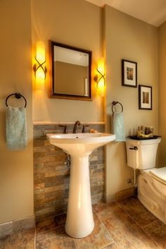 I like the sleek pedestal sink and the soothing lighting in this traditional powder room by Wallner Builders