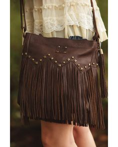 Messenger crossbody with studding across the front and flowy fringe all the way around. Features an adjustable shoulder strap, conceal and carry pocket and an inspirations quote on the inside of this super stylish bag.