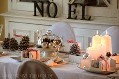 Stilvolle Tischdekoration mit Tannenzapfen, Silberkugeln, Kerzen & Hussen