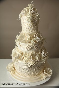 Ivory Swirls #13Luxe This is a fondant design made of three double tiers for extra height. An insert was placed between the first two layers to allow placement of the flowers and pearl ribbon. This cake is also decorated with an ornate swirl and textured paneling.