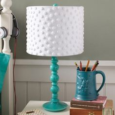 1. Pom Pom Shade  This makeover is so simple, yet so incredibly adorable! Pom poms are very cheap, in fact, you can often times find them at the dollar store.  Take some pom poms in whatever color you think will look best on your lamp and hot glue them to the shade.  It's a quick craft that won't take very long, but will have an awesome outcome.