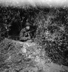 Machine gun toting American soldier in a foxhole near the front lines during the Battle of the Bulge.