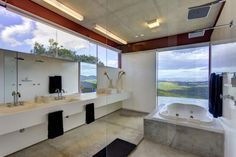 The bathroom as seen looking outward: concrete framed jacuzzi tub stands beside floor to ceiling glass panels, with panoramic views.