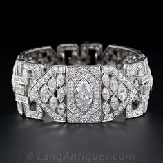 Platinum Diamond Art Deco Bracelet. A bright-white and gorgeous 2.40 carat antique marquise diamond, with the outline of a modern-cut 4.00 carat marquise, is the center of attention of this opulent and sensational, one inch-plus wide bracelet from the peak of the Art Deco period - circa 1925. Three main plaques, connected by three geometric 'slave links' sizzle with an artful array of twelve marquise diamonds and closely pave-set European-cut diamonds which frame the central marquise diamond...