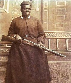 """Sepia-tone photograph of Mary Fields, holding a rifle. """"Stagecoach Mary"""" was the first African American woman to deliver U.S. mail on a star route, by horse-drawn cart and sometimes snowshoes in Montana winters. She was beloved in her adopted town of Cascade, MT. """"In 1959, actor and Montana native Gary Cooper wrote an article for Ebony in which he said: 'Born a slave somewhere in Tennessee, Mary lived to become one of the freest souls ever to draw a breath, or a .38.'"""""""