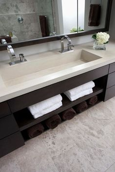 concrete trough sink, floating vanity with open space for towels, and mirror with storage behind.