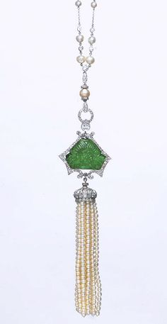 A PEARL, EMERALD AND DIAMOND NECKLACE   Designed as a seed pearl tassel, with an old European-cut diamond bombé cap, suspended from a carved emerald of floral design, within an old European-cut diamond scrolling frame, to the pear and old European-cut diamond and pearl surmount, with a fine-link chain, alternately-set with pearls and collet-set diamonds, mounted in platinum, 15 ins.