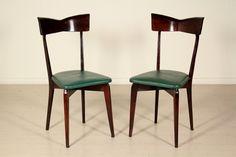 Coppia di sedie; legno tinto, imbottitura in espanso, rivestimento in similpelle. Buone condizioni, presentano piccoli segni di usura.