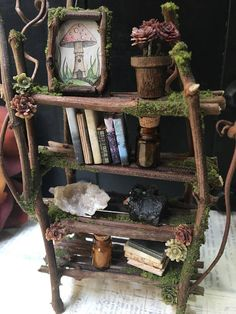 This little faery bookshelf is completely handmade, one of a kind, and would make a beautiful addition to any faery house or oddity shelf! Made with grapevine, moss, and lots of love :) Includes 16 accessories to decorate the shelves: 1 picture frame with my original artwork, 1 pot of flowers, 2 jars of tiny crystals, 1 geode crystal, 1 agate crystal, and 10 tiny wooden books! All items are loose so you can arrange them to your liking :) PLEASE NOTE: **This item is made to order** so the…