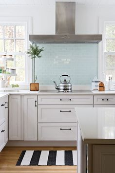 Absolutely gorgeous kitchen. Steel appliances, white cabinets, black handles, island, white walls, blue tile backsplash.. so open.