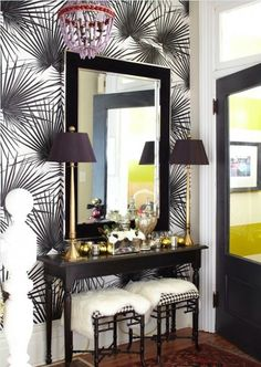 source: Meredith Heron Design  Chic, eclectic foyer with purple & red beaded chandelier, black & white wallpaper, slim black console table, gold buffet lamps, black faux bamboo stools ottomans and black mirror.