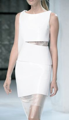 White shift dress layered over translucent fabrics with slicing at the waist…