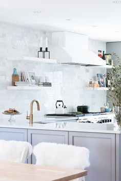 Modern kitchen with an open floor concept to maximize space, marble backsplash tiles, and a hood
