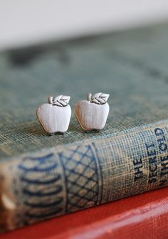 Teachers Pet Apple Studs  9.99 at shopruche.com. Simple and sweet, these silver colored apple earrings will add a touch of charm to your outfits.  .75'' length