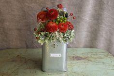 Lata de metal con flores de temporada