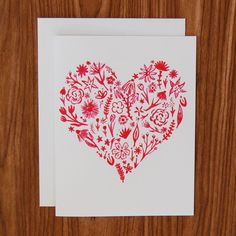 "This hand-painted card features floral blooms in the shape of a heart. The perfect card to keep on hand for a quick ""I love you"" or just because. Available as a single card paired with a 100% recycled"