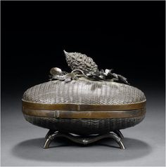 An oval bronze box and cover By Toun, Meiji Period Supported on two bamboo feet, the cover surmounted by a finial in the form of a large walnut lying on a bed of oak leaves, a cicada crawling atop, all reserved on a ground of simulated wickerwork, signed in a rectangular reserve Toun chu with kakihan.