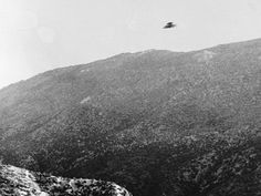 A UFO flying  over a mountain range.