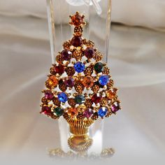 This #vintage Eisenberg Ice rhinetone Christmas tree brooch is gorgeous!  It features a gold tone Christmas tree with textured balls alternating with green, blue, yellow, re... #etsy #easter #spring #jewelry #jewellery #antiques #shopping