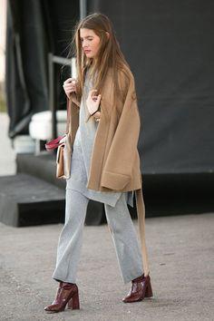 Mulher morena usa batom rosa queimado, moletom cinza mescla, botas de verniz vinho e maxi casaco camelo