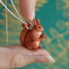 Finely detailed, miniature, hand-sculpted red squirrel pendant. The squirrel has rusty-red multi-tonal textured fur, and he holds a tiny acorn. Let me know in the note to seller section at checkout if you would prefer not to have an acorn. If you want you can also request a