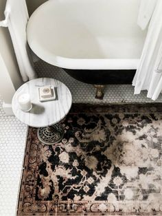 Amazing bathroom features black claw foot tub paired with white marble top accent table over black and pink Persian rug layered over vintage hex tile floor.