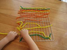 Weaving and developing fine motor skills by weaving pipe cleaners through a cooling rack. Brilliant! Plus cheap re-usable fun