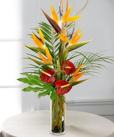 """Tropical Paradise""  This showy, exotic bouquet stands tall, with its lovely Birds of Paradise and red Anthurium blooms."