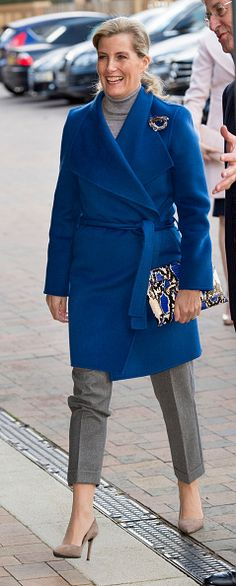 Sophie, Countess of Wessex looked super chic in cropped grey trousers, a grey polo neck and bold blue coat.  She accessorized her look with a snakeskin clutch and nude court shoes as she arrives to open Portesbery School in Camberley.