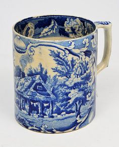 A LATE 18TH/EARLY 19TH CENTURY BLUE AND WHITE POTTERY TANKARD decorated with a lake scene and having a thatched cottage in the foreground and a castle in the background, 10cm diameter x 11cm in height