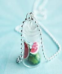 """This necklace features a jar pendant of lemons sculpted from polymer clay. The glass jar measures about 2.5 cm tall and is securely attached to a silver tone ball chain necklace that measures 24"""" in l"""