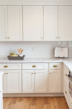 White shaker cabinetry with brass cups and knobs - by Rafterhouse.