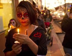 15-year-old Luna Sotelo with her face painted walks in the procession as the Chicano Arts Council held it's Dia de los Muertos festival on Friday,