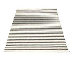 Flot, stribet gulvtæppe fra Pappeline. Farverne er et mix af hvid, beige, brun og grå.