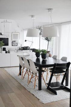 Las sillas eames blancas con una mesa negra tienen un contraste fabuloso en tu living comedor