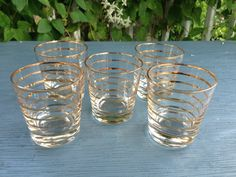 This is a set of seven (5) five gold striped glass rock tumblers, sure to complement any MidCentury Modern bar cart.