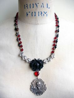 """Custom Skull Necklace with Mother of Pearl Let's start with the pendant portion, shall we? The rose is a vintage repurposed brooch. I hung a vintage mother of pearl bead from the rose to the """"star"""" of this necklace, a repurposed vintage advertising watch fob with a skull and crossbones on the front and, on the back it says..."""