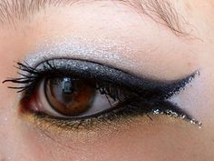 Gold, silver and black sparkly eye makeup with a double cat eye flick. Rock n roll