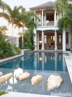 In a Vero Beach, Florida house decorated by Thomas Hamel, the living room opens to the pool. Coral stepping stones at one end let you walk on water.