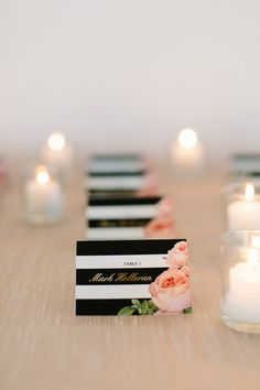 Wedding escort card idea - black and white striped escort cards with gold foil text + pink floral accent {Megan Clouse Photography}