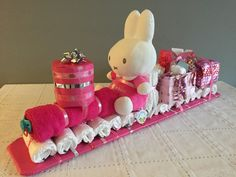 Luiertrein voor een meisje | Benodigdheden: 15 luiers, maat 2, voor het onderstel, 1 roze handdoek, 1 speen, 1 roze Nijntje, 1 kerstbal 'my first christmas' voor de voorkant, 1 roze mandje voor de cadeautjes, 1 kubus voor het achterstel, 10 meter gekleurd lint, 1 stuk laminaat voor de onderkant | Succes en veel plezier met geven!