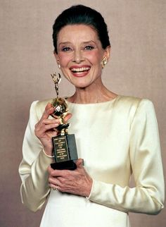 A grinning Audrey Hepburn poses with her Cecil B. Demille award at the The 47th Annual Golden Globe Awards, 1990.
