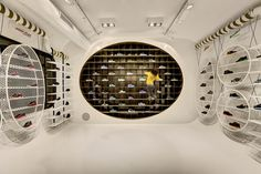 Display modules composed of iron, plexy and wooden materials are hung with simple details on the coloured constructive round duct which is assembled to white coloured polyurethane finished surrounding surfaces that evoke a curvilinear formed tunnel.