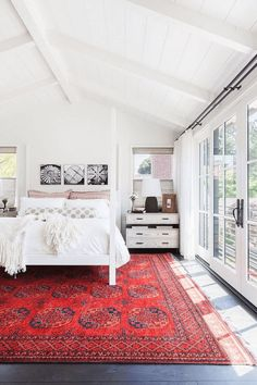 White bedroom with bright red rug, black accents, pantone flame Comic con master bedroom Area rug