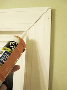 Don't use the brown wood filler on white trim - use white paintable door, window and trim caulk to fill our cracks and nail holes (Dap brand is among the easiest to work with).