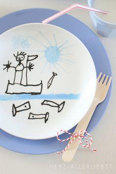"""Ich habe sie also mit Malunterlagen, Malkitteln, Porzellan-Stiften und den alten Tellern an den Küchentisch gesetzt und sie machen lassen. OK, der hellblaue Stift hat dieses """"Machen lassen"""" nicht überlebt, doch dafür haben wir jetzt echte Künstlerteller im Haus."""