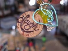 """Wine glass charm made from wine cork with """"Laugh"""" written on it."""
